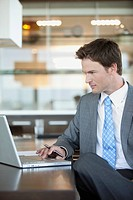Businessman using laptop at desk in office