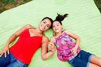 Mother and daughter lying on blanket, holding hands