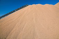 Conveyor belt over mound of sand at quarry