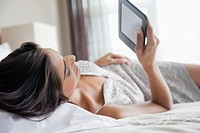 Young woman lying on bed and using digital tablet