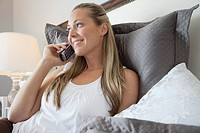 Young woman in bed talking via phone
