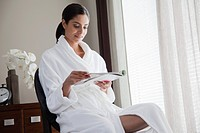 Young woman wearing bathrobe and reading magazine