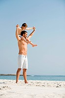 Father carrying son on his shoulders on a beach