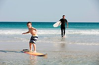 Young boy surfing in shallow water