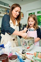 Mid adult woman baking with daughter in kitchen