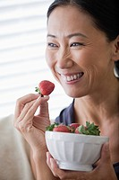 Smiling woman eating strawberries