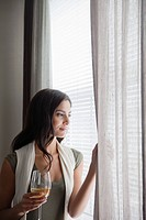 Woman looking through window and holding wine glass (thumbnail)