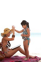 Mother Looking at Daughter´s Hand on Beach Blanket, Aruba