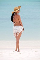 Woman in Floppy Hat and White Fringe Fabric Wrapped Around Waist on beach, Portrait, Aruba