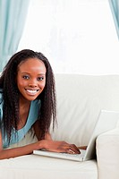 Close up of smiling woman lying on the couch with her notebook
