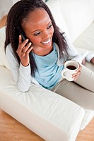 Smiling woman on the phone having a cup of coffee