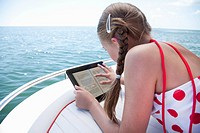 USA, Florida, St. Petersburg, Girl 10_11 using digital tablet on yacht