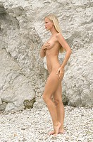 Naked young woman on rocks                                                                                                                            ...