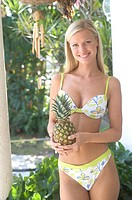 Young woman in bikini with pineapple                                                                                                                  ...