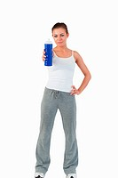 Sporty woman with hand on her hip offering a sip of water against a white background
