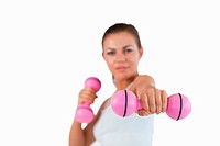 Healthy woman working out with dumbbells against a white background