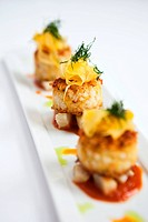 Crab cakes with artichoke and fennel salad served with tomato sauce