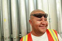 Portrait of skilled worker with sun glasses taking a break on construction site
