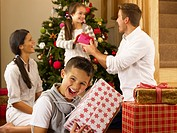 Hispanic family exchanging gifts at Christmas