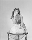 Young woman pointing on globe, smiling, portrait