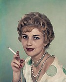 Woman smoking cigarette, smiling, portrait