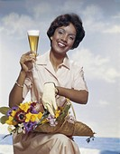 Woman holding flowers basket with beer glass, smiling, portrait