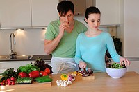 Young couple in kitchen preparing salad