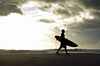 Silhouette of a surfer walking with his surfboard along the beach with stormy clouds in the background, Tarifa, Andalucia, Spain