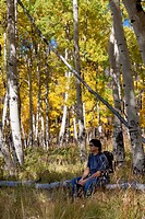 Asian man sitting on a log enjoying a beautiful grove of aspen trees with yellow leaves in autumn in Colorado
