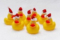 flock of rubber ducks wearing santa claus hats on artificial snow