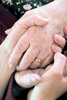 Geriatric care. Carer holding an elderly person´s hands. Photographed in France.
