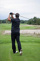 A golfer teeing off, rear view
