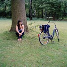 A woman relaxing under a tree next to a bicycle