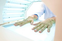 Phototherapy booth. Patient with their hands in a phototherapy box.