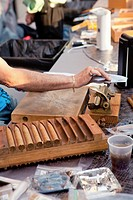 Man using tools in cigar making factory