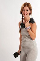 Young woman, redhead, exercising with weights in the gym to get fit