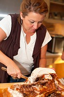 Woman is carving a turkey at Thanksgiving