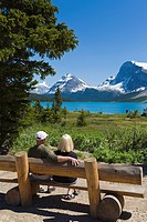 Couple on a bench overlooking, Bow Lake, Icefields Parkway, Alberta, Canada