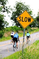 cyclists passing a slow caution sign on a road
