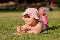 The little girl laying on a grass in park, drawing in a writing