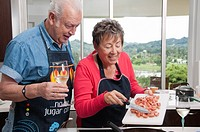Senior Hispanic couple cooking together in kitchen