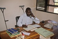 Kenya, Homa Bay, Oyugis DDCU. Techno Serve project using animal draft power for farming, man working at desk in office.