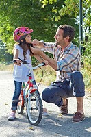 Father closing the helmet of her daughter on a bike