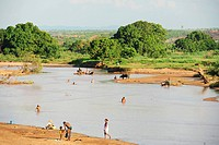 Madagascar, Mampkony, children playing on sandbank of red_colored river