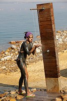 Young girl making shower on the dead sea, Jordan