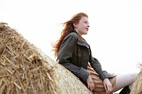 Teenage girl resting on haybales