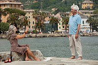 Senior couple taking photograph by the water, Italy, Rapallo