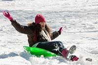 Hispanic girl sledding on snow covered hill
