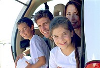 Smiling family sitting together in hatchback of car