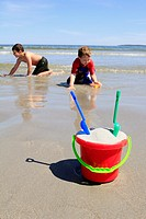 kids playing in the sand at the beach behind a sand bucket
